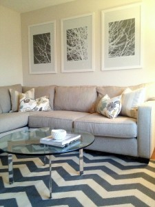 interior-sweet-white-wooden-frames-artwork-portray-at-white-wall-painted-over-cool-l-shaped-grey-fabric-sectional-sofas-with-cute-white-cushions-as-well-as-smart-round-glass-coffee-table-over-chic-che